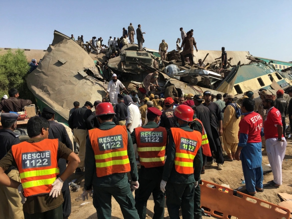 Rescue workers stand as people gather at the site following the accident. [Stringer/Reuters]